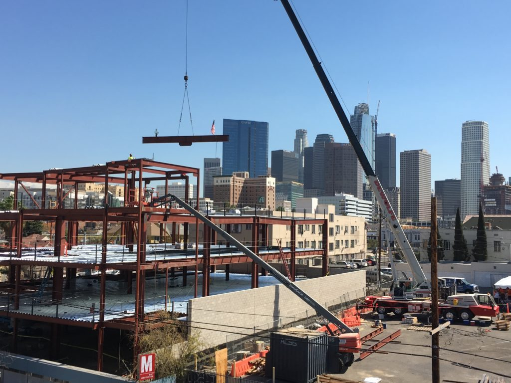 steel beam lifted by crane onto legal aid foundation of los angeles building