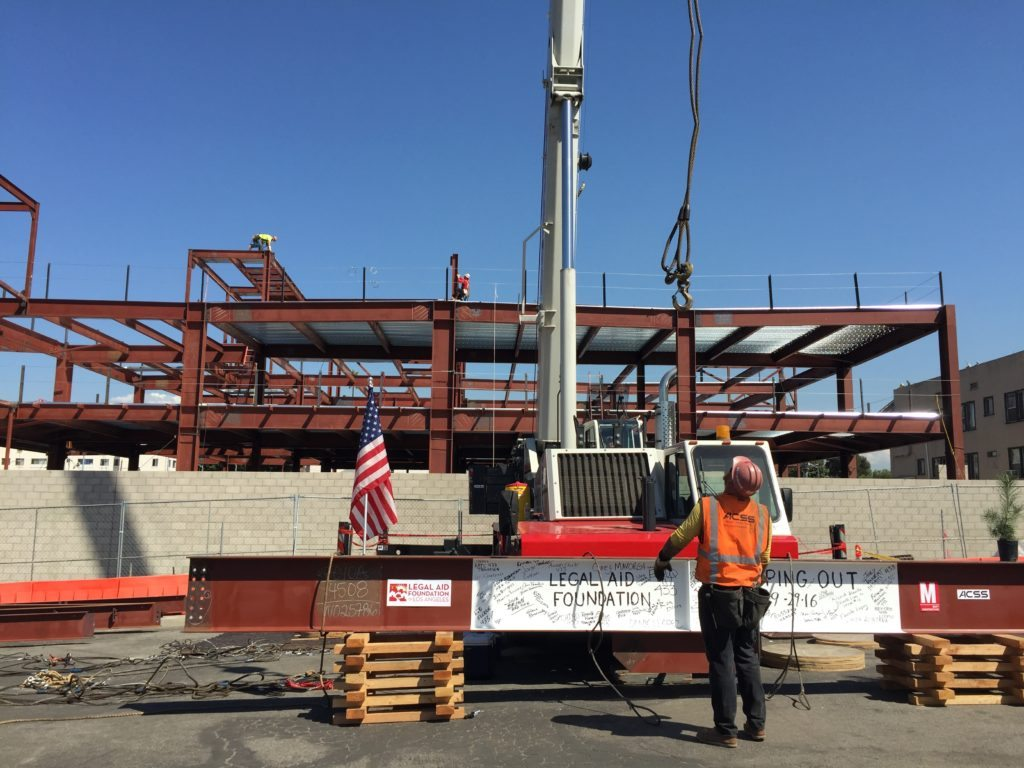 worker preparing steel beam for crane lift los angeles legal aid foundation topping out