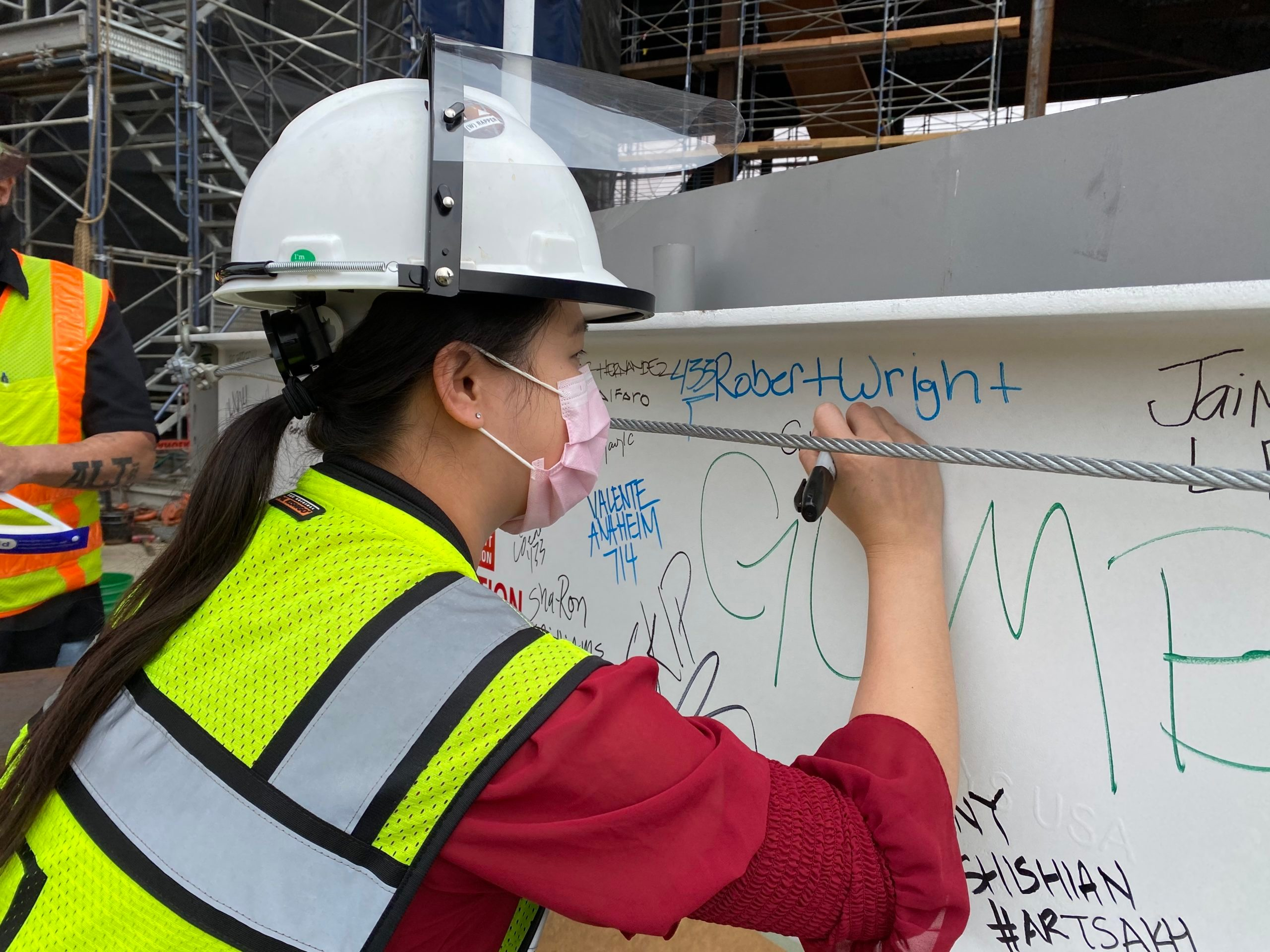 Project Manager, Cory Kuo, signs final steel beam at the (w)rapper